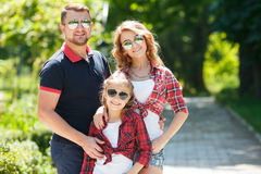 Happy family spends together the weekend. Young happy family of three having fun together outdoor. Pretty little daughter. Parents and girl look happy and smile Royalty Free Stock Photos