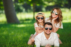 Happy family spends together the weekend. Young happy family of three having fun together outdoor. Pretty little daughter. Parents and girl look happy and smile Stock Photo