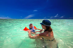 Happy family splashing in green lagoon on a tropical resort Stock Photo