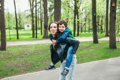 Happy family in spring park. Young mother and her son spending time outdoor on a summer day. Happy family in spring park. Young mother and her five year old son stock photo