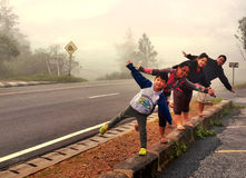Happy Family. Stand on one leg, open arms, and smiling faces in the cold weather in Thailand Royalty Free Stock Photo