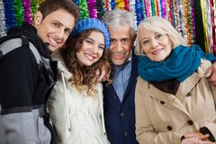 Happy Family Standing Against Tinsels At Store Royalty Free Stock Photo