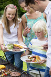 Happy family standing at barbecue grille Stock Photos