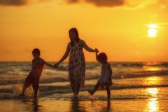 Happy family standing on the beach Stock Image