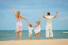 Happy family standing at the beach Royalty Free Stock Photos