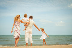 Happy family standing at the beach Stock Photos