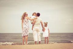 Happy family standing at the beach Stock Photo