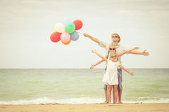 Happy family standing on the beach at the day time. Stock Image