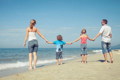 Happy family standing on the beach at the day time. Stock Photography