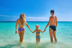 Happy family standing on the beach at the day time Royalty Free Stock Image
