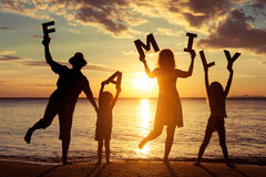 Happy family standing on the beach at the sunset time. Stock Photos