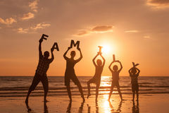 Happy family standing on the beach at the sunset time. Royalty Free Stock Images