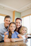 Happy family standing behind the kitchen counter Stock Photography