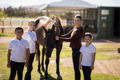 Happy family standing with a brown horse in the ranch Stock Photo