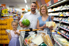 Happy family standing with full cart in supermarket Royalty Free Stock Photography