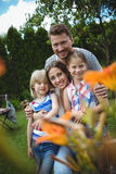 Happy family standing on grass in park on a sunny day Royalty Free Stock Image