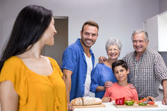 Happy family standing in the kitchen stock photos