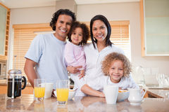 Happy family standing in the kitchen together Stock Photo