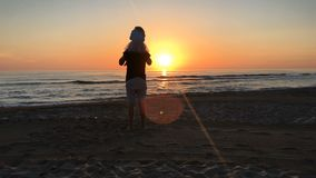 Father and daughter standing on the seashore at sunset. stock footage
