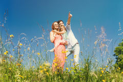 Happy family standing on meadow in summer Stock Image