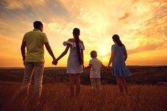 A happy family is standing in the nature at sunset in the evenin stockfotografie