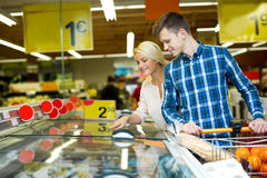 Happy family standing near display with frozen food Stock Image