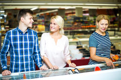 Happy family standing near display with frozen food Royalty Free Stock Photo