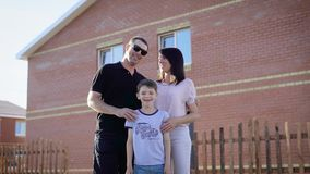 Happy family standing near their house in sunny summer day embracing each other. Father, mother and son feeling glad stock video