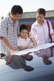 Happy family standing next to the car and looking down at the map Royalty Free Stock Image