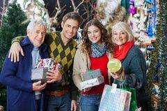 Happy Family Standing Together In Christmas Store Stock Photo