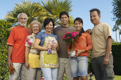 Happy Family Standing Together In Garden Stock Photo