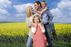 Happy family standing together near field of yellow blooming flowers Stock Images