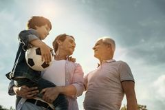 Happy family standing together and smiling. Feeling proud. Exuberant smiling loving daddy son and grandfather looking at each other while the dad holing his son Stock Images