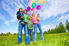 Happy family stands with balloons in park Stock Photos