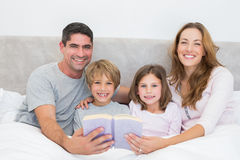 Happy family with storybook in bed Stock Images