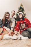 Happy family in stylish sweaters and cute dog at christmas tree. With lights and gifts. atmospheric festive moments. merry christmas and happy new year concept Stock Images