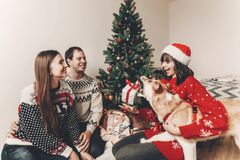 Happy family in stylish sweaters and cute dog having fun with gi. Fts at christmas tree with lights. atmospheric emotional moments. merry christmas and happy new Stock Images