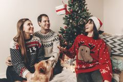 Happy family in stylish sweaters and cute funny dog exchanging g. Ifts at christmas tree with lights. emotional moments. merry christmas and happy new year Royalty Free Stock Photography