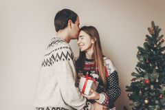 Happy family in stylish sweaters exchanging gifts in festive roo. M with christmas tree and lights. emotional moments. merry christmas and happy new year concept Stock Image