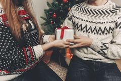 Happy family in stylish sweaters exchanging gifts in festive roo. M with christmas tree and lights. emotional moments. merry christmas and happy new year concept Royalty Free Stock Image