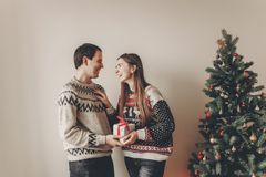 Happy family in stylish sweaters exchanging gifts in festive roo. M with christmas tree and lights. emotional moments. merry christmas and happy new year concept Royalty Free Stock Photos