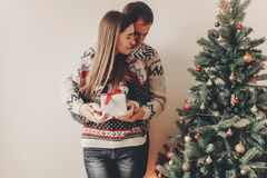Happy family in stylish sweaters exchanging gifts in festive roo. M with christmas tree and lights. emotional moments. merry christmas and happy new year concept Royalty Free Stock Images