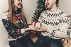 Happy family in stylish sweaters exchanging gifts in festive roo. M with christmas tree and lights. emotional moments. merry christmas and happy new year concept Royalty Free Stock Photography