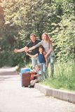 Happy family with suitcase traveling hitchhiking. Happy family with suitcases stopping a passing car Stock Photography
