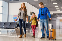 Happy family with suitcases in airport. Let journey begin. Portrait of cute couple with their son at airport walking down hall with suitcases Stock Photography