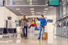Happy family with suitcases in airport. We love traveling. Happy family with kid in airport having fun while waiting for boarding Stock Photo