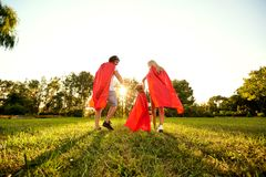 Happy family in suits of superheroes in the park at sunset royalty free stock images