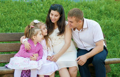 Happy family in summer city park outdoor, pregnant woman, parent and children, bright sunny day and green grass, beautiful people Royalty Free Stock Photos