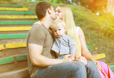Happy family in  summer day. Parents kiss and child Stock Photos