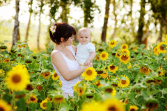 Happy family in summer field of beautiful sunflowers Stock Photo